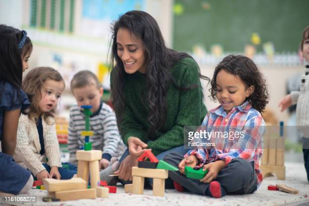 teacher playing with students - preschool student stock pictures, royalty-free photos & images