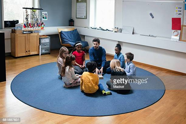 teacher playing with students while sitting on floor at school - montessori education stock pictures, royalty-free photos & images