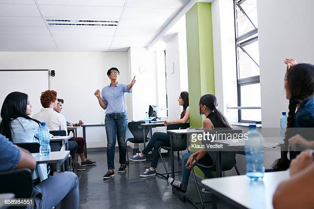 Teacher pointing at student with raised hand