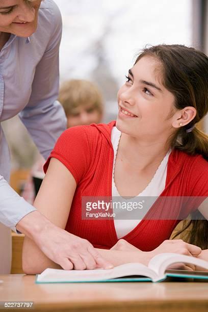 professora, apontando para reservar menina olhando pelo professor - parte do meio - fotografias e filmes do acervo