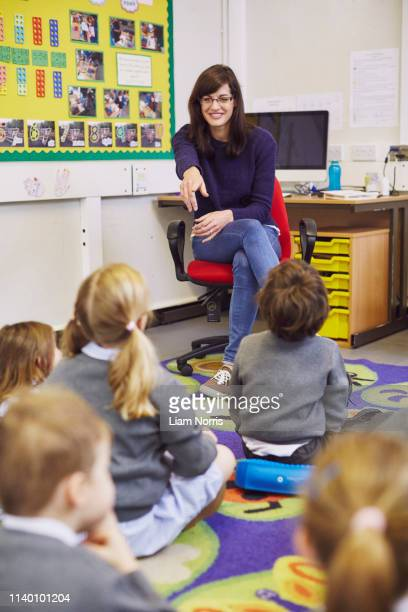teacher pointing to children sitting on floor in elementary school classroom - demonstration stock pictures, royalty-free photos & images