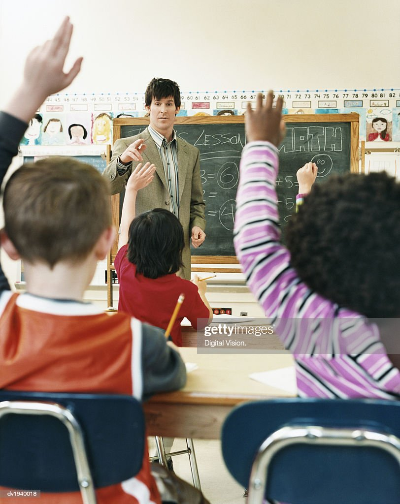 Teacher Pointing to Primary School Students With Raised Hands in a Classroom : Stock Photo