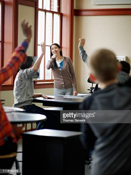 Teacher pointing to students with hands raised