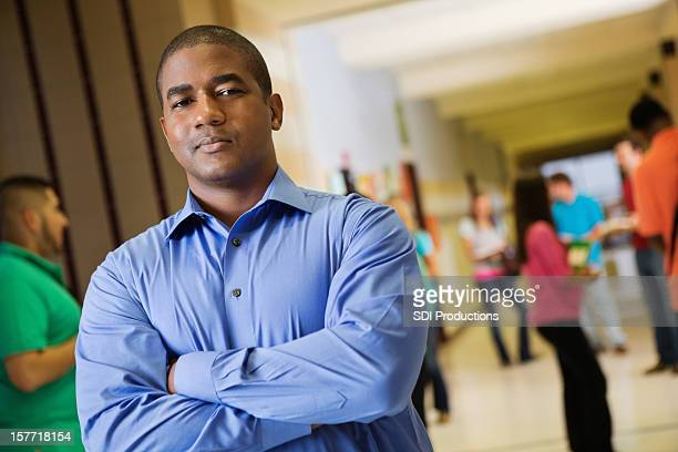 Teacher posing in busy high school hallway between classes