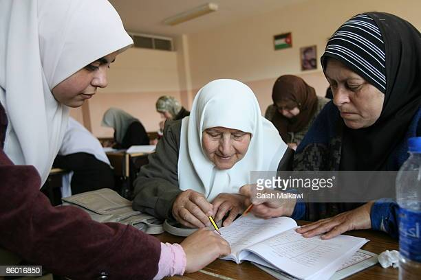 Teacher Raeda Harasees helps her students to read the alphabet in a classroom of 12 women of different ages all eager to learn to read and write at...