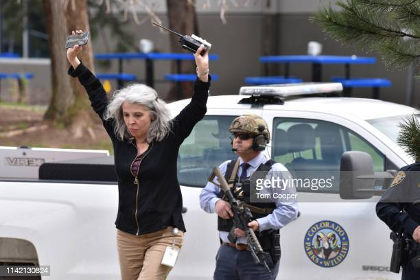 A teacher raises her arms as she exits the scene of a shooting in which at least seven students were injured at the STEM School Highlands Ranch on...