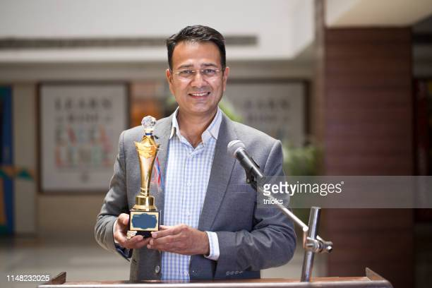 teacher raising trophy and giving speech - awards ceremony stock pictures, royalty-free photos & images
