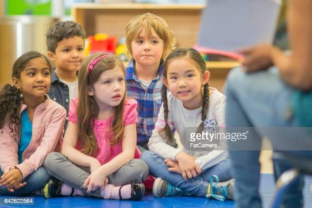 Lehrer liest ein Buch für ihre Schüler