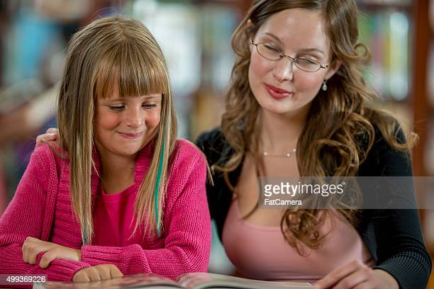 Teacher Reading a Book with a Student