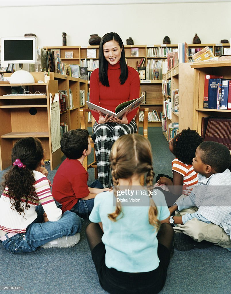 Teacher Reading a Story Book to a Small Group of Children in a Library : Stock Photo