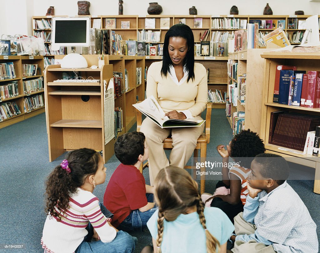 Teacher Reading a Story Book to Children in a Library : Stock Photo