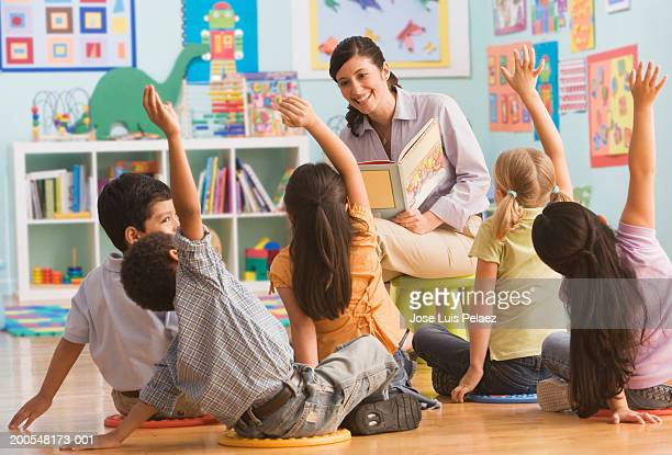 teacher reading book in classroom, children (2-7) raising hands - preschool child stock pictures, royalty-free photos & images