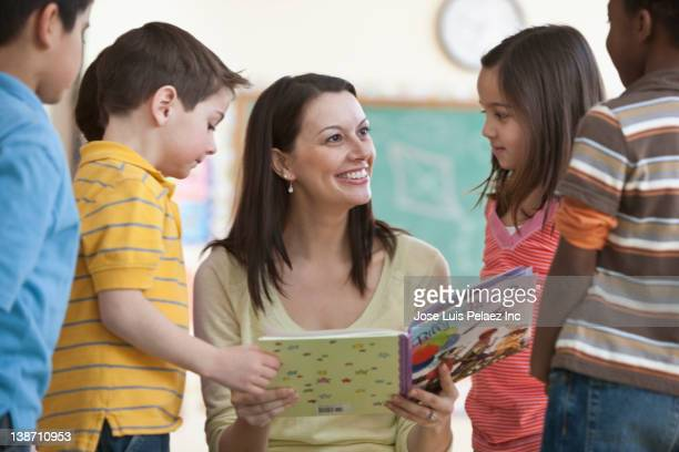teacher reading book to students - elementary age stock pictures, royalty-free photos & images