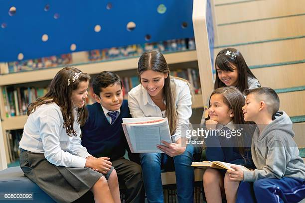 Teacher reading books to a group of students