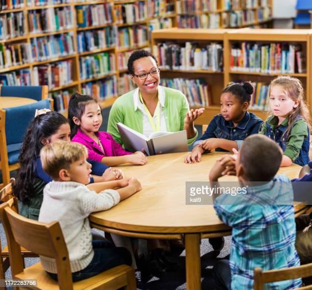 lehrer lesen kindern in der bibliothek - bibliothekar stock-fotos und bilder