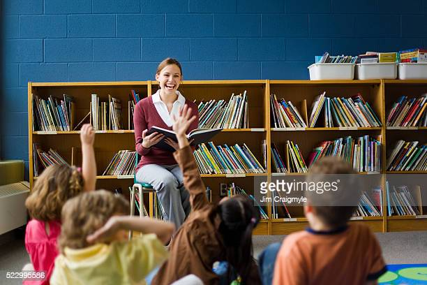 teacher reading to class - bibliothekar stock-fotos und bilder