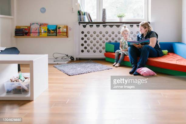 teacher reading to girl in playschool - nursery school child stock pictures, royalty-free photos & images