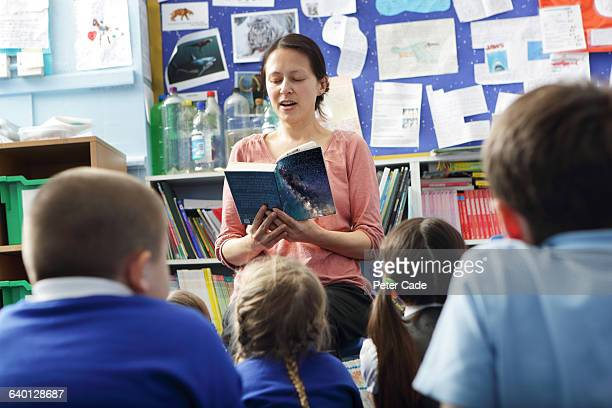 teacher reading to pupils in class - teacher stock pictures, royalty-free photos & images