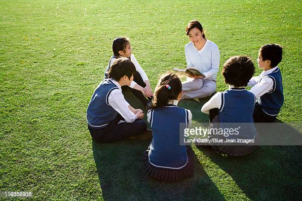 Teacher reading to students on grassy field