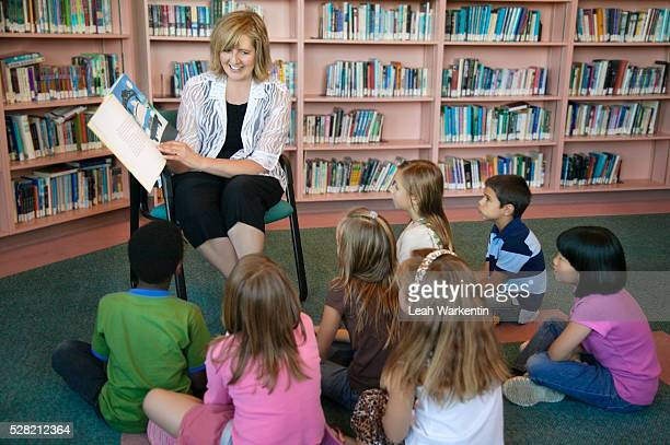 teacher reading to students - storyteller stock pictures, royalty-free photos & images