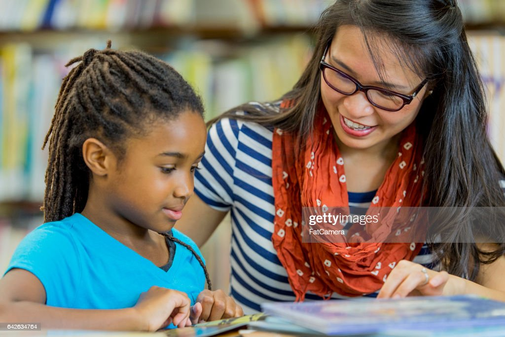 Teacher Reading with a Student : Stock Photo