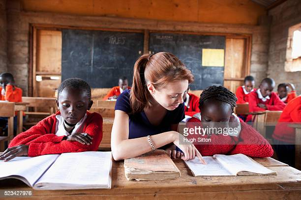 teacher reading with school children in classroom, kenya - hugh sitton stock pictures, royalty-free photos & images