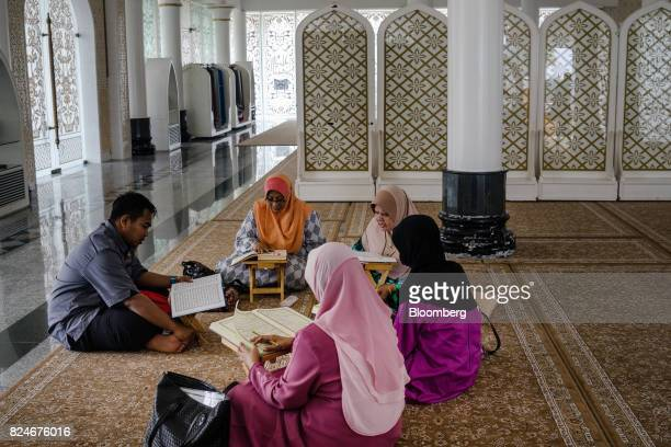 A teacher reads religious texts with visitors at the Crystal Mosque in Kuala Terengganu Terengganu Malaysia on Monday July 23 2017 With a federal...