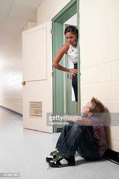 teacher reprimanding student in hallway
