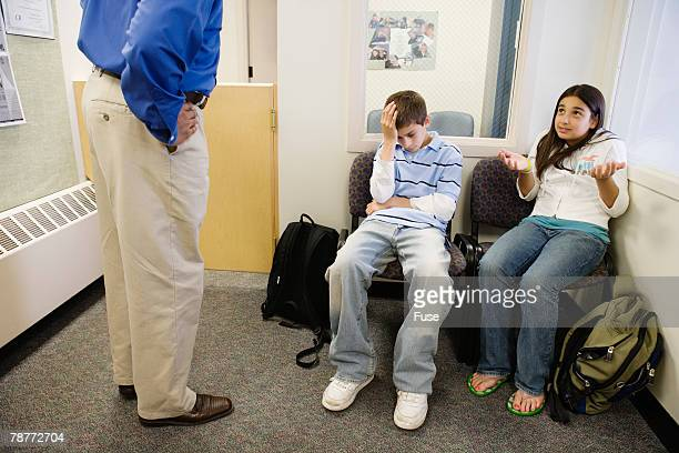 teacher reprimanding two students - restraining stock photos and pictures