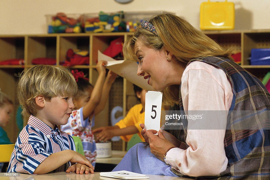 Teacher reviewing numbers with student : Stockfoto