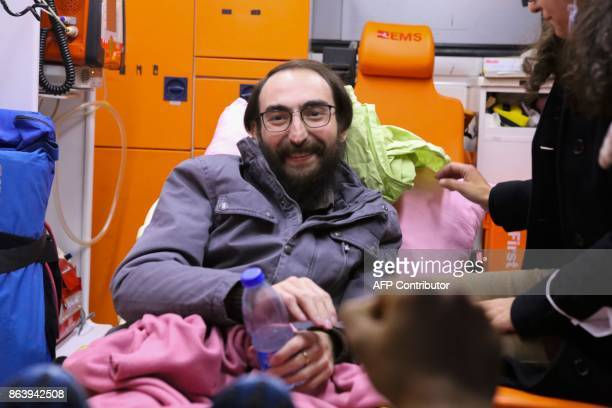 Teacher Semih Ozakca smiles on a stretcher inside an ambulance after being released on parole from the Sincan prison on October 20 2017 in Ankara A...