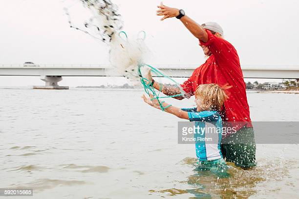 teacher showing boy how to use cast net, sanibel island, pine island sound, florida, usa - estuary stock pictures, royalty-free photos & images