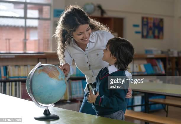 professor que mostra países em um globo a um menino na escola - geografia física - fotografias e filmes do acervo