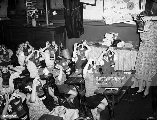 A teacher showing her class how to use a gas mask in a classroom at Cosway Street LCC primary school in Marylebone London 27th June 1941 The LCC...