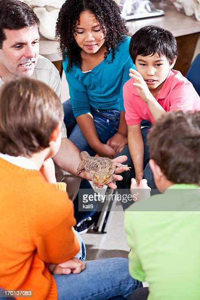 Teacher showing reptile to students