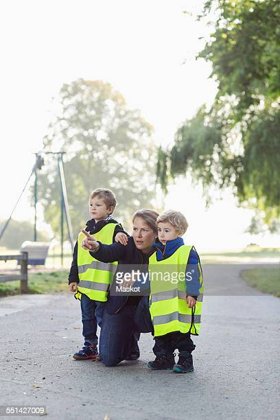 Teacher showing something to children while pointing away at playground