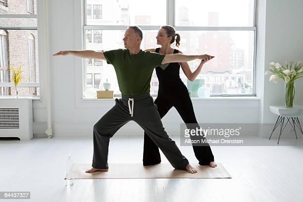 teacher showing student yoga move
