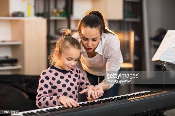 teacher showing to a child how to play the piano - electric piano stock photos and pictures