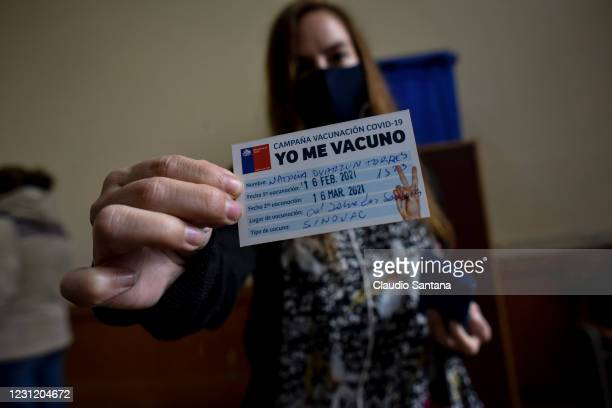 Teacher shows an identification card during the vaccination against COVID-19 , at Abdon Cifuentes school on February 16, 2021 in Santiago, Chile. The...