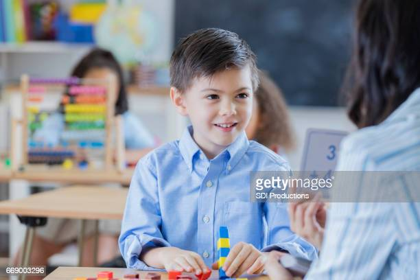 Teacher shows flash cards to young male student