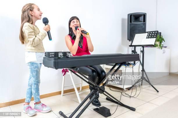 lehrer-sänger mit klavier assisting girl student in singing, blick auf den text auf tv-bildschirm - sängerin stock-fotos und bilder