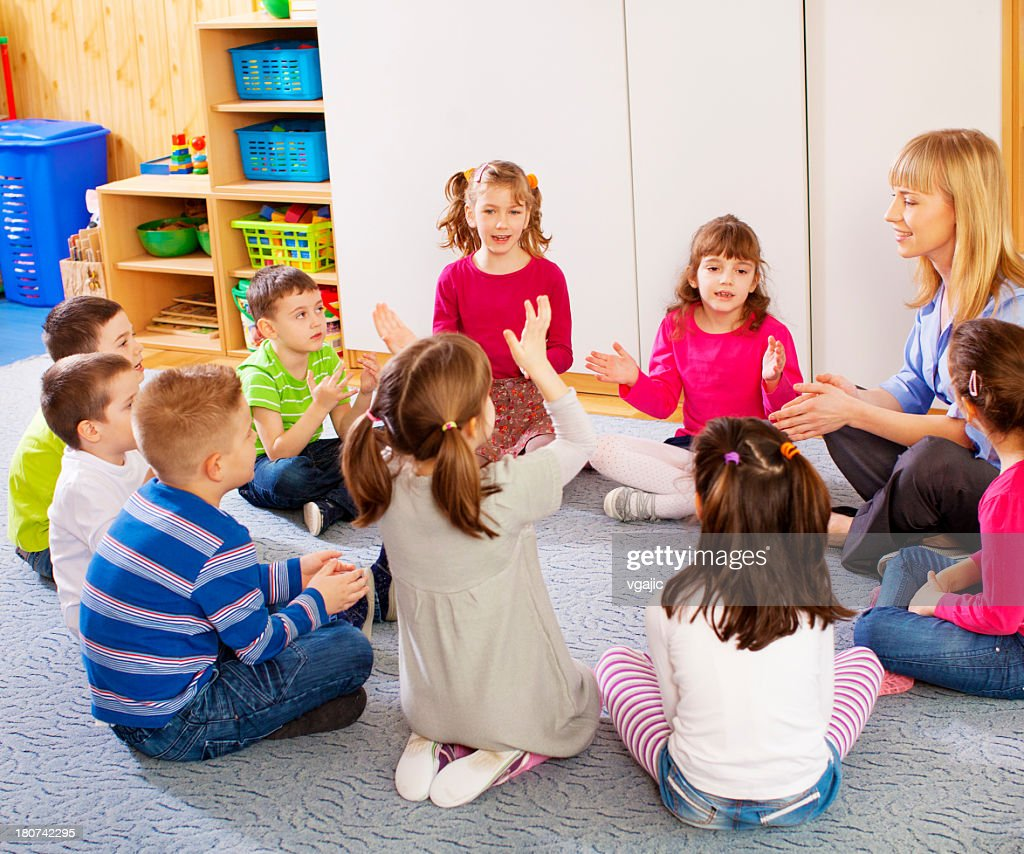 Teacher singing with children. : Stock Photo