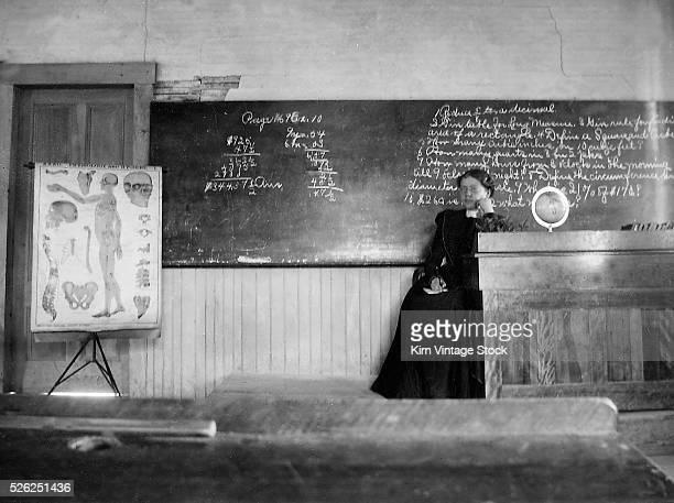 Teacher sits in her classroom ca 1900