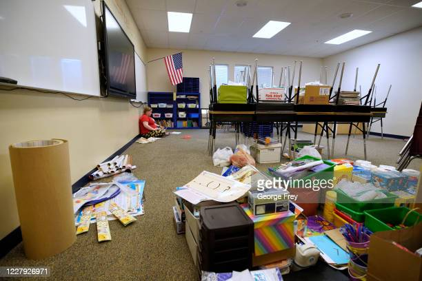 A teacher sits on the floor as she starts to reset up her classroom with new rules on social distancing at Freedom Preparatory Academy as they begin...