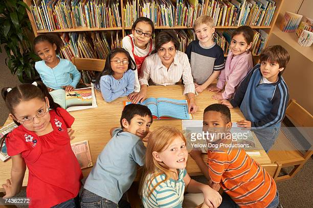 Teacher sitting at table surrounded by children (9-10, 10-11) in school library, elevated view