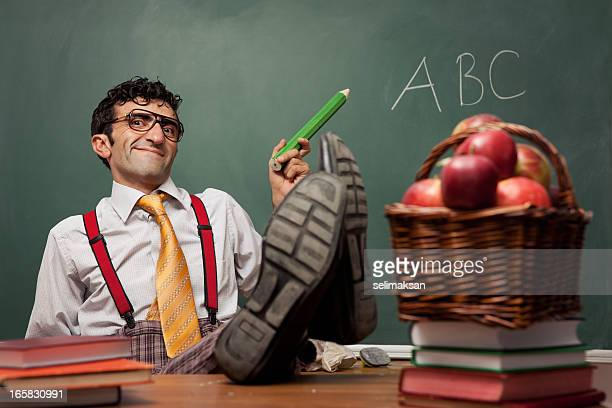 Teacher sitting in classroom and having his legs on desk