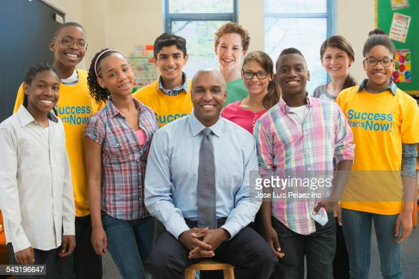 Teacher smiling with volunteers and students in classroom
