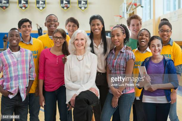 Teacher smiling with volunteers and students in gymnasium