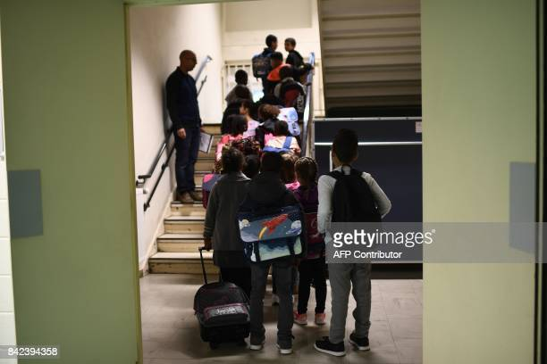 A teacher speaks to his pupils in a corridor prior to enter in a classroom at a primary school at the start of the new school year on September 4 in...