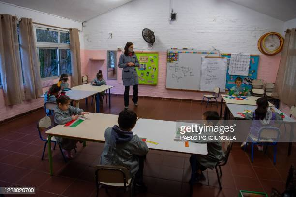 Teacher speaks to pre-school children during a class in a public school in Montevideo, amid the COVID-19 novel coronavirus pandemic, on August 11,...